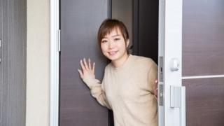 ドアから顔出す女性
